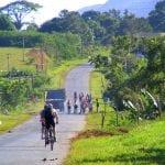 Radtour durch Kuba entlang asphaltierter Straße durch grüne Landschaft