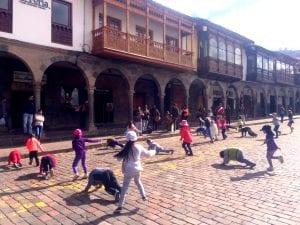 Kinder machen Sport auf der Plaza de Armas in Cuzco und werden im Hintergrund musikalisch begleitet