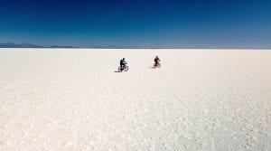 Zwei Biker fahren auf der weißen Salzwüste dem Horizont entgegen
