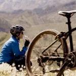 Bikerin entspannt im Hintergrund mit blick auf die Berge, vor ihr ein eMountainbike im Bild