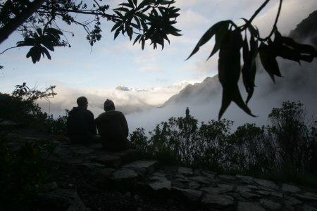 zwei Wanderer bewundern sitzend den Ausblick auf die wolkenverhangenden Anden in Peru