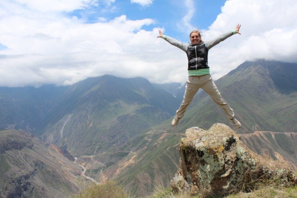 Mitarbeiterin Springt gestreckt vor dem Colca Tal in die Luft