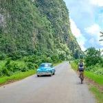 Radfahrerin auf Straße mit Oldtimer in Viñales