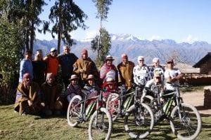 Gruppenfoto zum Abschied mit den Dorfbewohnern von Misminay und unseren ebikes, im Hintergrund schneebedeckte Bergketten