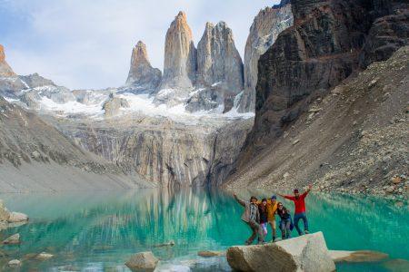 fünf Wanderer posieren auf Fels vor den Cuernos-Spitzen im Torres del Paine
