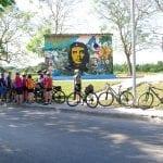 Radgruppe hält im Baumschatten vor einem Che Guevara-Schild