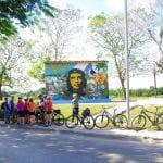 Radgruppe in Kuba vor Schild mit Che Guevara