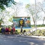 Radgruppe hält im Schatten vor einem Guevara Denkmal auf Kuba