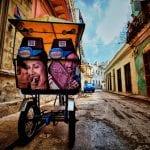 Bici-Taxi von hinten in runter gekommener Straße in Havanna