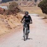 Touristin fährt auf Bike entlang einer staubigen Straße in Peru