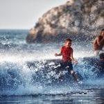 Kubanischer Junge im Meer spielt in den Wellen