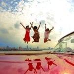 Drei Frauen springen am Hafen von Havanna hinter einem Oldtimer fröhlich in die Luft