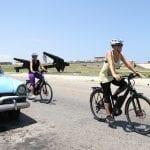 Zwei Radfahrer auf einer Straße in Kuba mit Oldtimer
