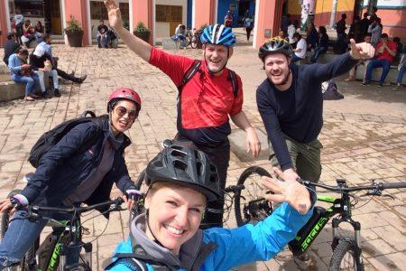 4 eBiker winken in ein Selfie auf Platz von Bogota