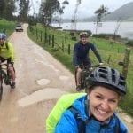 Drei Radfahrer lachen trotz Regen in die Kamera am See Suesca