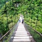 Menschen an der Hängebrücke an der Wasserfallroute neben dem Pailon de Diablo