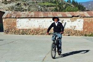 HuancaAuf der Plaza in Huanca test ein Schuljunge freudig ein eBike