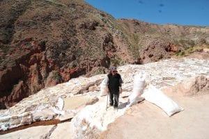 Älterer Mann arbeitet in den Salzminen von Maras und steht hier in einem umgepflügten Salzbecken neben ein paar Säcken, die mit Salz gefüllt sind