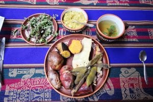 Traditionelles Pachamanca-Dorfessen aus dem Erdofen: auf dem Teller viele verschiedene Kartoffelsorten und unterschiedliche Saucen und Dips