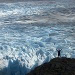 Wanderer steht vor Gletscher mit Armen über dem Kopf im Torres del Paine NP