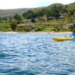 Kajaker in gelbem Kajak bei Tour auf dem Titicaca See
