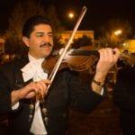 Mariachi in typischer Kleidung spielt am Abend Geige in Mexiko
