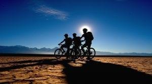 Drei Biker stehen vor Sonnenuntergang in der Pampa El Leoncito