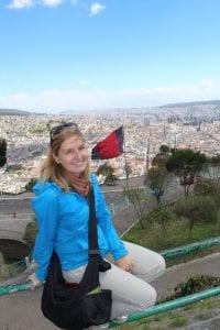 Mitarbeiterin sitzt hoch oben auf Aussichtspunkt mit der großen Stadt Quito im Hintergrund