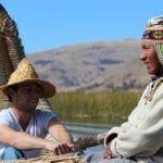 Tourist und Einheimischer auf Schilfboot im Titicaca-See
