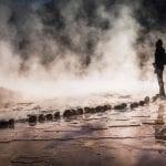 Ein Tourist steht bei Dunkelheit direkt an den Geysiren von El Tatio im Norden Chiles
