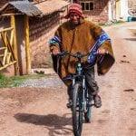 Traditionell gekleideter Peruaner probiert voller Freude unserre eMountainbikes aus