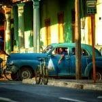 Blauer Oldtimer vor bunter Häuserfront in Havanna