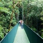 drei Touristen stehen auf Hängebrücken über dem Regenwald in Costa Rica