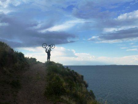 Biker am Titicaca-See hält Rad in die Luft