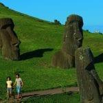 Pärchen läuft an Moais vorbei auf der Osterinsel in Chile
